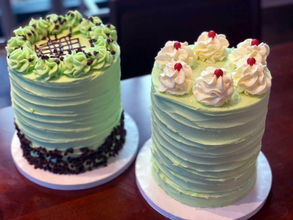 two custom white and green cakes on pink trays