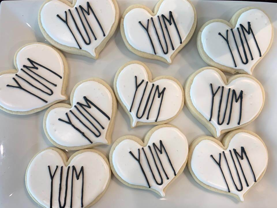 white heart cookies with yum lettering