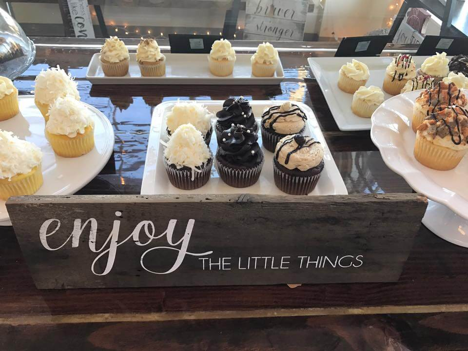 cupcake display with enjoy the little things sign
